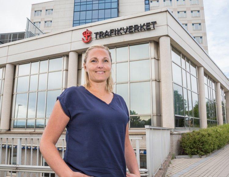 Martina Karlsson står utomhus framför Trafikverkets byggnad, iklädd en blå t-shirt.