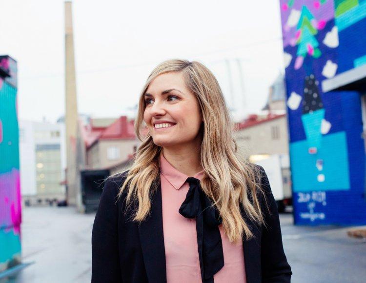Susannah Sjöberg står bland några byggnader varav ett par är målade med grafitti.