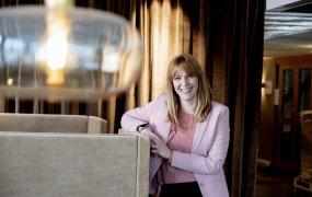 Andrea Cedwall, transaktionschef på Hemsö, står och lutar sig mot en beige sammetssoffa och ler stort mot kameran. I förgrunden syns en fin glaslampa som hänger i taket och sprider ett varmt sken. Bakom Andrea hänger lyxiga bruna sammetsdraperier.