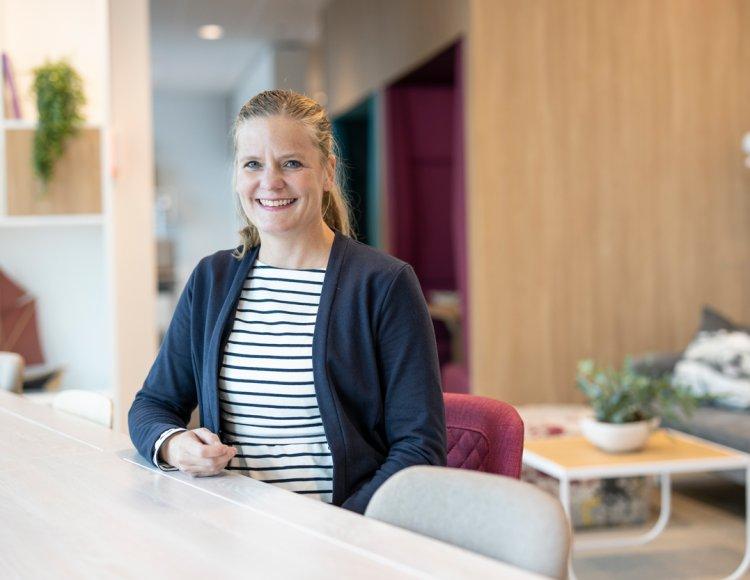 Malin Sjödahl sitter på ett kontor vid ett avlångt bord med en soffgrupp i bakgrunden.