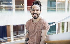 Farhad Johari tittar med ett leende in i kameran ståendes i Trappan i SEBs stora och luftiga lokal.