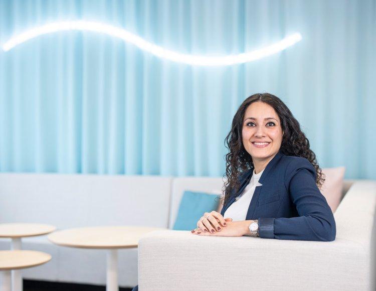 Fahimeh Farhadian sitter i en ljus soffa, bakom hänger en ljusblå gradin och ovanför hänger en ljusslinga