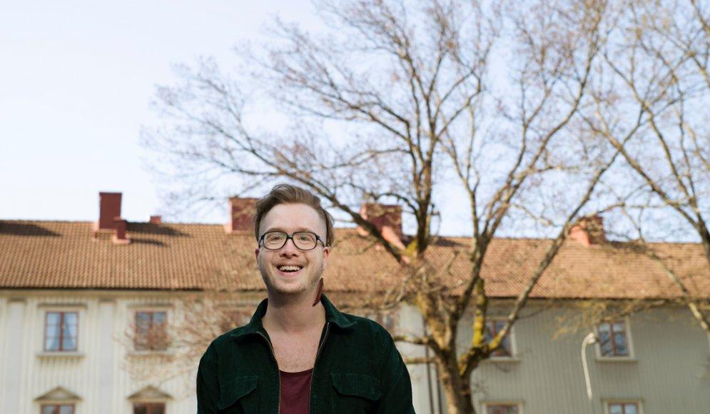 Mattias Jägerskog står utomhus, med lägenhetshus och träd i bakgrunden.