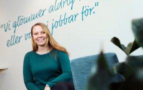 Jessica Hultgren, elektroingenjör på Göteborg Energi, sitter på kontoret och ler mot kameran. I förgrunden syns en turkos stol och en krukväxt, och på väggen bakom henne står det skrivet