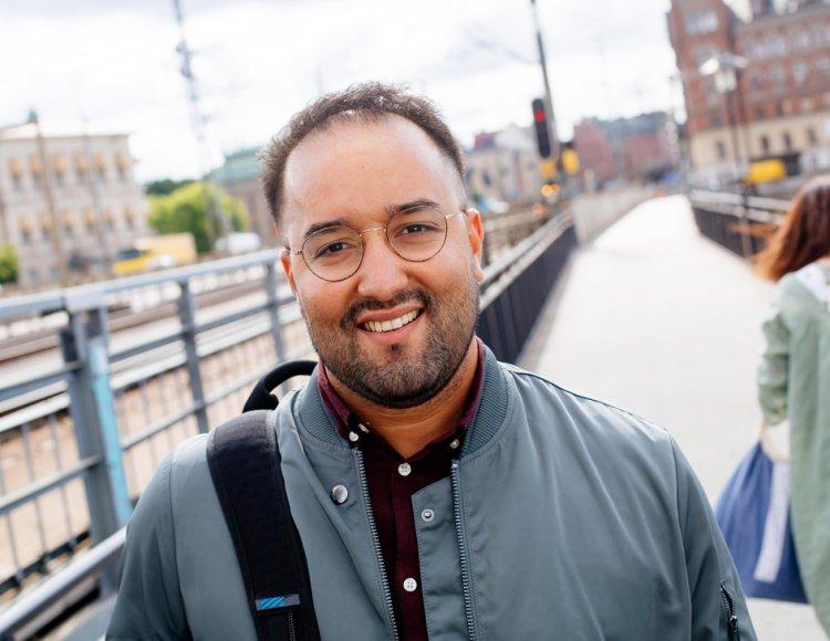 Khalid Raouz står utomhus på en gångväg längs med järnvägsspår i centrala Stockholm.