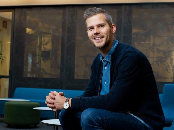 Andreas Palm sitter vid en soffgrupp med små bord i bakgrunden.