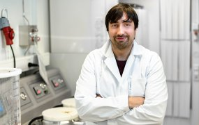 Christopher Karlsson står i ett labb iklädd vit rock och skyddsglasögon.
