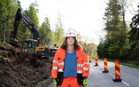 Elise Ekliden står utomhus på en väg i skogen med ett pågående grävarbete och en grävmaskin i bakgrunden.