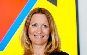 Madeleine Gössner, kommunikationschef på ALTEN, står framför företagets färgglada logga.