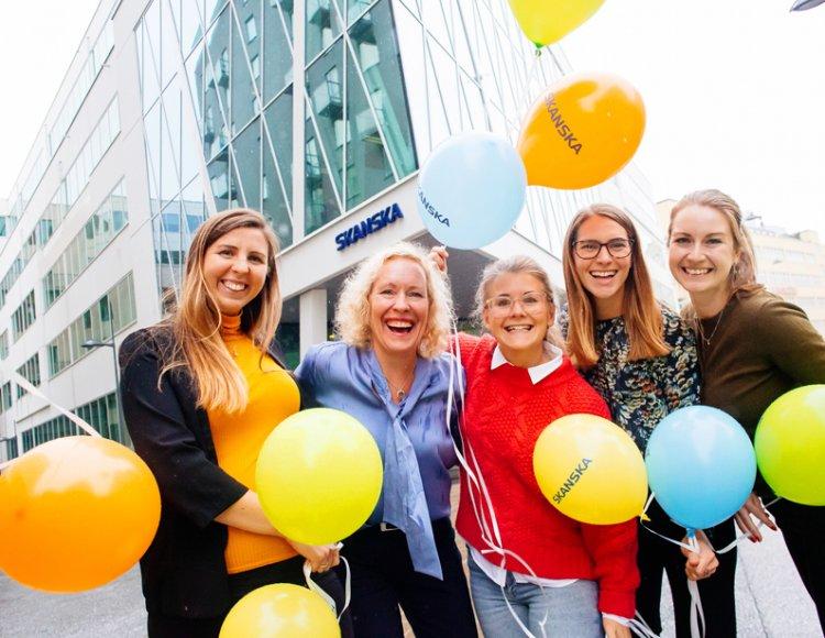 Ann Ericsson står utanför Skanskas lokaler tillsammans med fyra kollegor, omringade av ballonger.