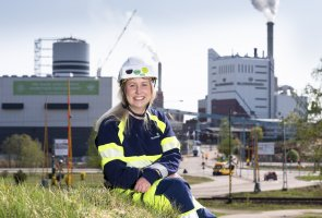 Gruppchefen Tina Jonasson sitter i gräset på en kulle framför BillerudKorsnäs stora fabriker.