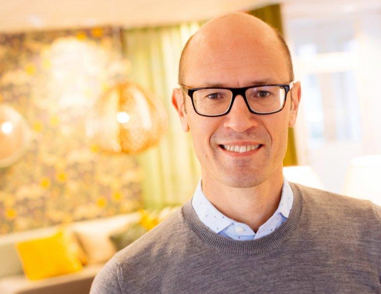 Stefan Sandberg står i Uppsalahems lokaler med en soffgrupp i bakgrunden.