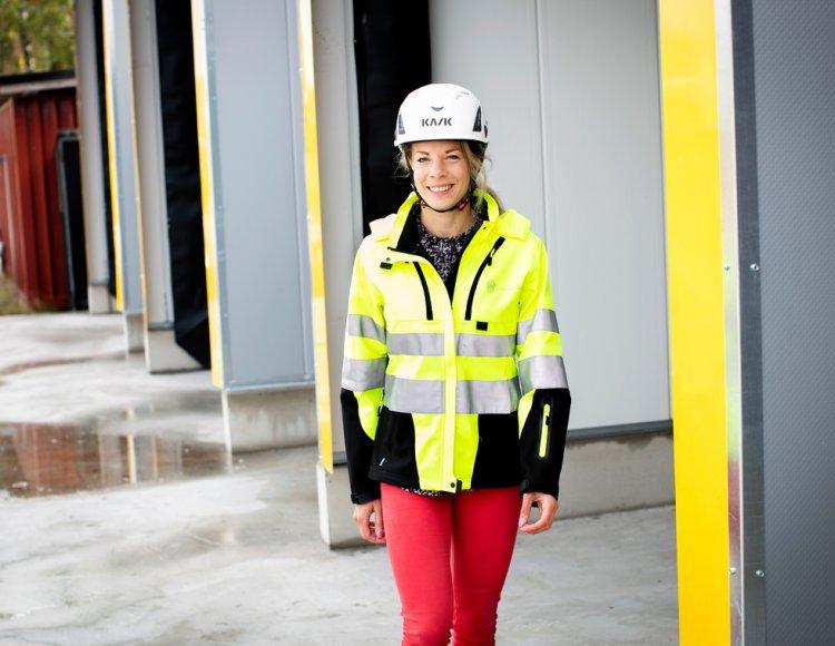 Vanja Karlsson går i skyddsjacka och hjälm utanför en av Fortifikationsverkets lokaler.