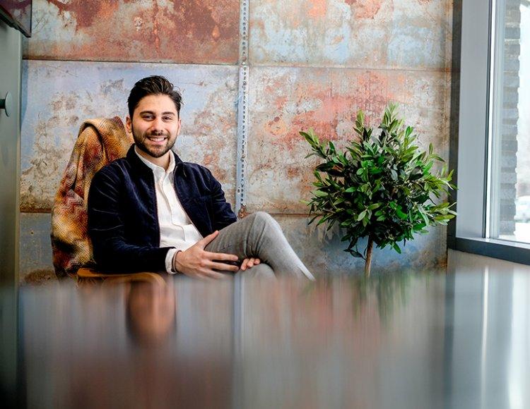 Arvin Bahmani, trainee inom projektutveckling, sitter på ett kontor. Väggarna är klädda med någon slags rostig plåt och bredvid honom står ett litet olivträd. Det ser trendigt ut. Till höger syns ett fönster.