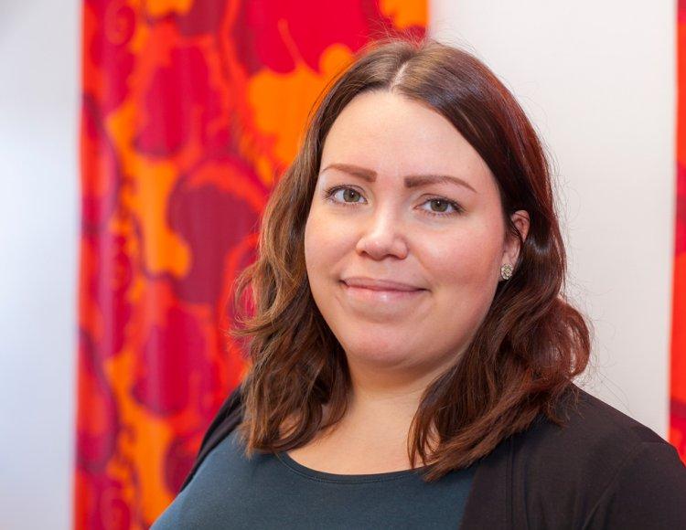 Lisa Rapp på LKAB. Hon ler mot kameran och bakom henne hänger ett rödmönstrat tyg. Det ser ut att vara inne på ett kontor.