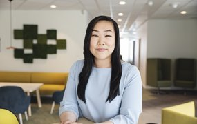 Jennifer Quach sitter i en kontorsmiljö med färgglada möbler och tittar in i kameran.