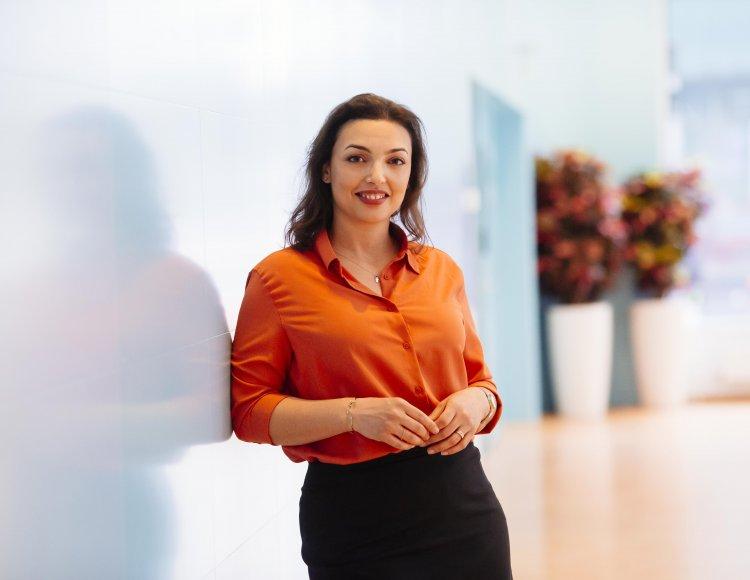 AlexandraDonnersMuhammed klädd i en stark orange skjorta, lutad mot en ljus vägg i Vattenfalls ljusa och luftiga lokal.