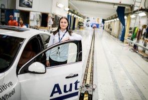 Hanna Karlsson står bredvid en bil med ena armen lutandes mot bildörren, i Autolivs testrum.
