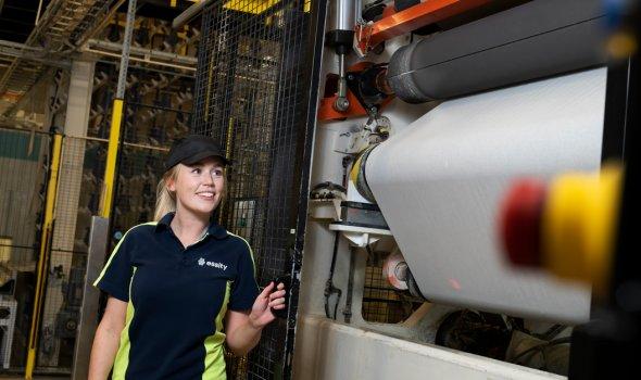 Linnea Jörgner står intill en maskin i en hall på Essity.