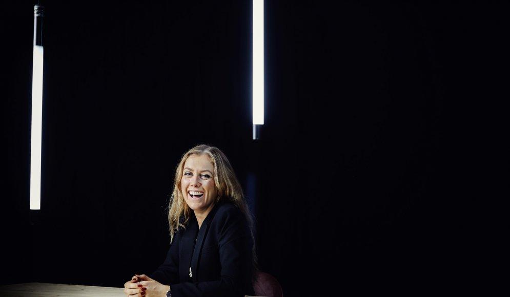 Carolin Solskär sitter i en studio med två  neonrör hängandes från taket och svart bakgrund.