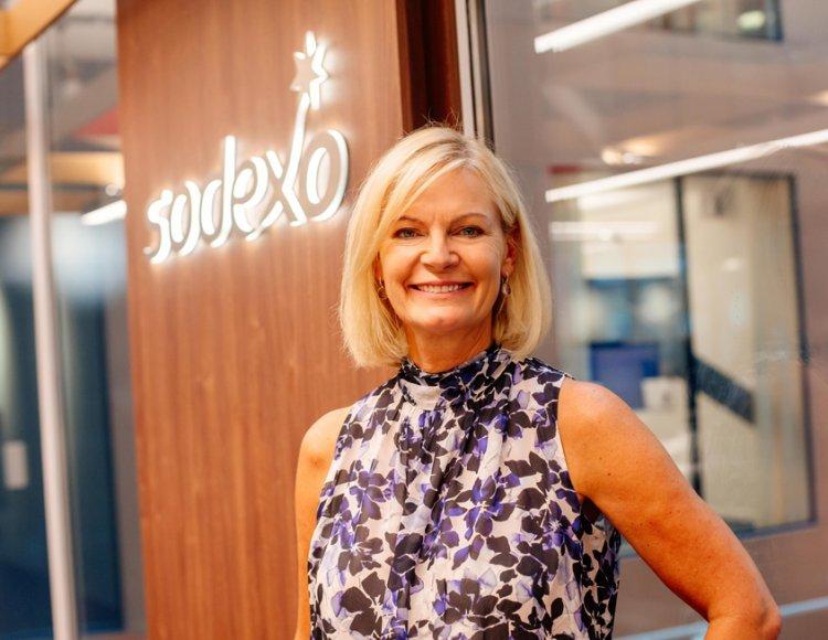 Eva Kristensson, kommunikationsdirektör på Sodexo ståendes framför en träpanel inne i Sodexos luftiga lokal.