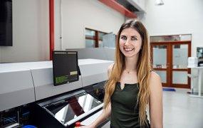 Johanna Malmström, mekatronikingenjör och projektledare på Mycronic. Hon står i något slags lab framför en till synes avancerad maskin med flera skärmar. Hon ler mot kameran.