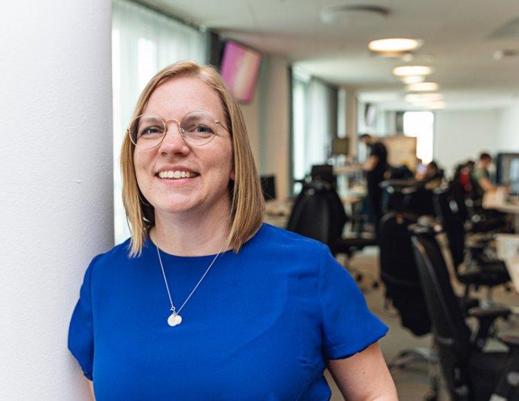 Katarina Palm, gruppchef på Tre, står i ett öppet kontorslandskap och ler mot kameran. I bakgrunden kan man skymta några av hennes kollegor.