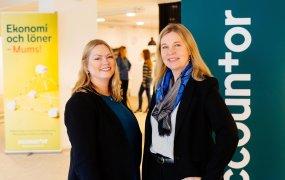 Anna-Karin Lindeberg och Sofie Bley Claesson står i en lokal med flera Accountor-bilder i bakgrunden.