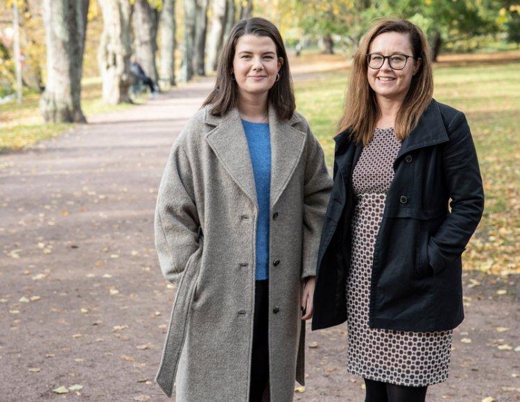 Felicia och Åsa står utomhus på en gångväg i en park med höstträd i bakgrunden.