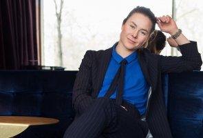 Serena Mon de Viennes sitter i en soffa med korsade ben, med fönster i bakgrunden.