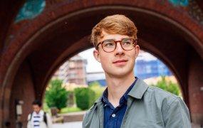 Axel Backlund fotad i utomhusmiljö klädd i blå piké och grå skaljacka. I Bakgrunden skymtar en tegelbyggnad och bostadsområde.