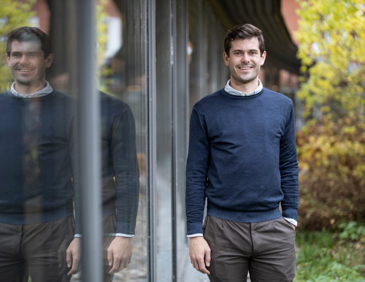 Emil Nordander står utanför Tetra Paks lokaler längs stora fönster.