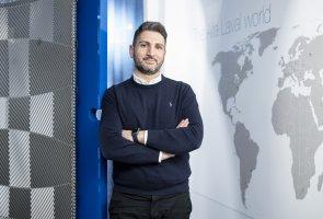 Senan Rasoul på Alfa Lavals kontor ståendes framför en vägg med världskartan som motiv.