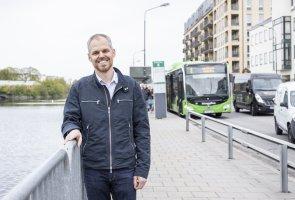 Fredrik Holmlund på Trafikverket står utomhus på en bro och håller i räcket. Han ler mot kamera. Bakom honom syns en grön buss från Skånetrafiken.