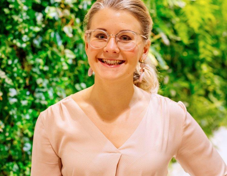 Sofie Jonsson står framför en vagg av gröna växter.