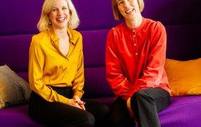 Jessica Levander och Maria Jalvemo sitter i färgglada blusar i en stor lila soffa.