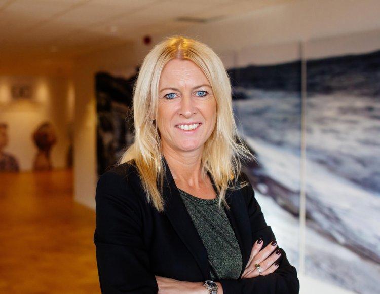 Eleonor Öhlander står i en korridor med ett stort fotografi i bakgrunden.
