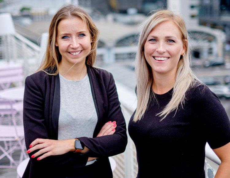Johanna Nargell och Emma Lemón, kollegor på Business Sweden, står utomhus på en takterass med utsikt över staden.