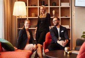 Linda, Ulf och Elisabeth står, respektive sitter i ett hemtrevligt personalrum.