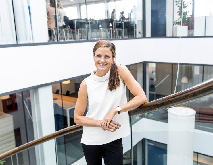 Sara Järdler, Head of Employer Branding på PwC står lutandes mot räcket i trappan inne på företagets ljusgård klädd i vit topp, och svarta jeans.