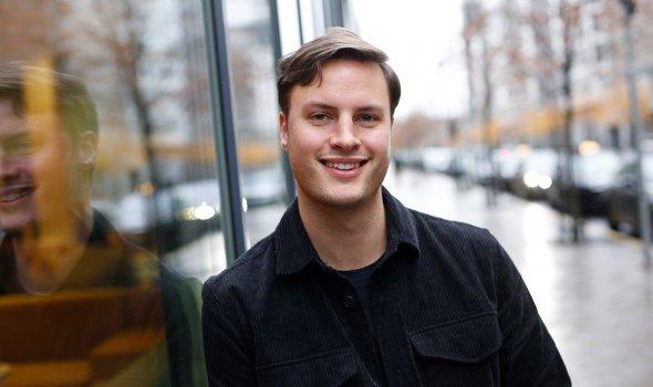 Gustav Frid står utanför Vattenfalls lokaler, lutad mot ett stort fönster.