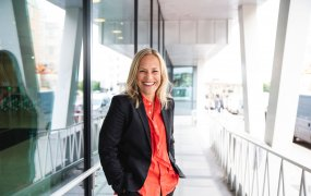 Anna Wenner, HR-chef på Skanska ler in i kameran. Hon står utomhus i solen, i bakgrunden skymtar parkerade bilar.