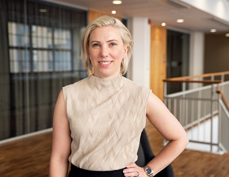 Malin Nilsson ståendes i Deloittes stilrena lokaler