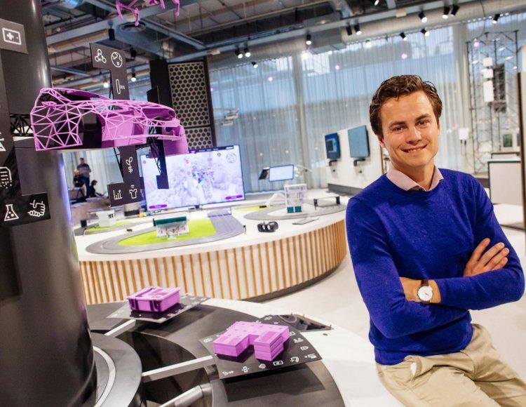 Adam Hemlin Billström lutar sig mot en bänkskiva i en lokal med olika innovativa teknikprylar i bakgrunden.