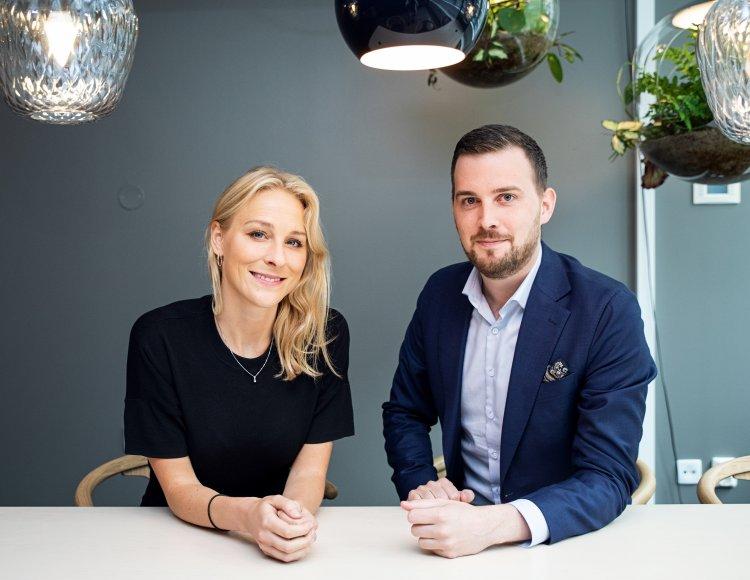 Johanna Widegren & Marcus Örtengren  sitter i Grant Thornton lokaler vid ett vitt stort konferensbord. I taket hänger lampor och växter i olika former.