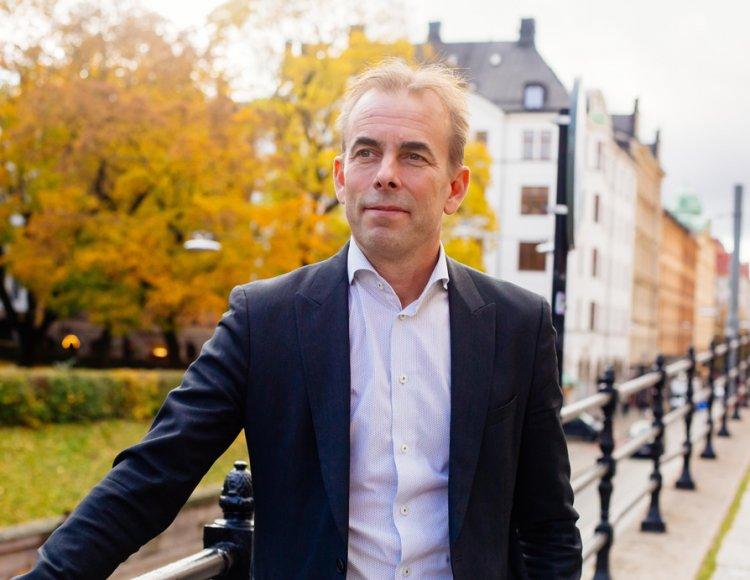 Johan Färnstrand står utomhus på en gångbro med höstträd och byggnader i bakgrunden.