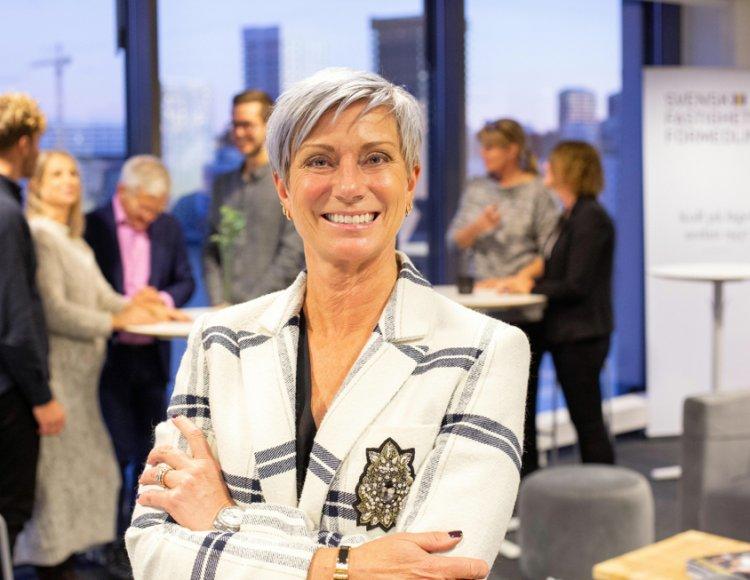 Liza Nyberg står på ett Svensk Fastighetsförmedling-kontor med kollegor i bakgrunden.