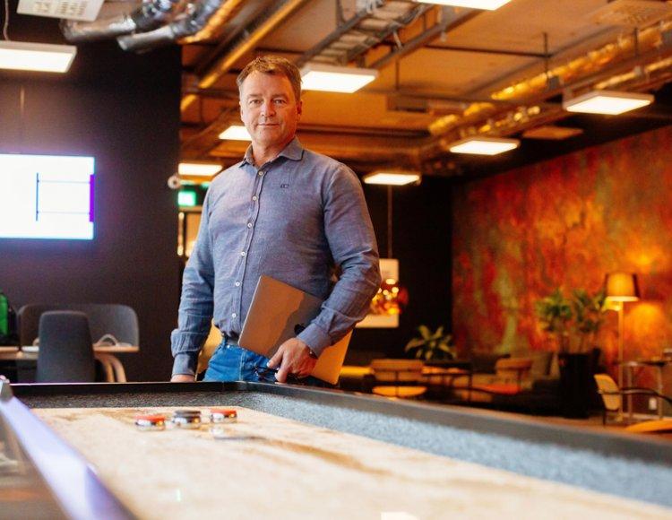 Lars Billström står i en gemenskapslokal med ett shuffleboard i förgrunden.