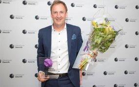 Consats vd Martin Wahlgren framför fotoväggen under Universum Awards med priset Årets Employer branding-företag i handen.