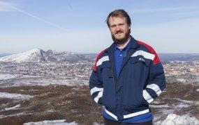 Petter Madsen jobbar som utvecklingsingenjör på LKAB. Han står högt upp på ett delvis snötäckt fjäll. Bakom honom skymtar man Kiruna. Solen skiner på en blå himmel.